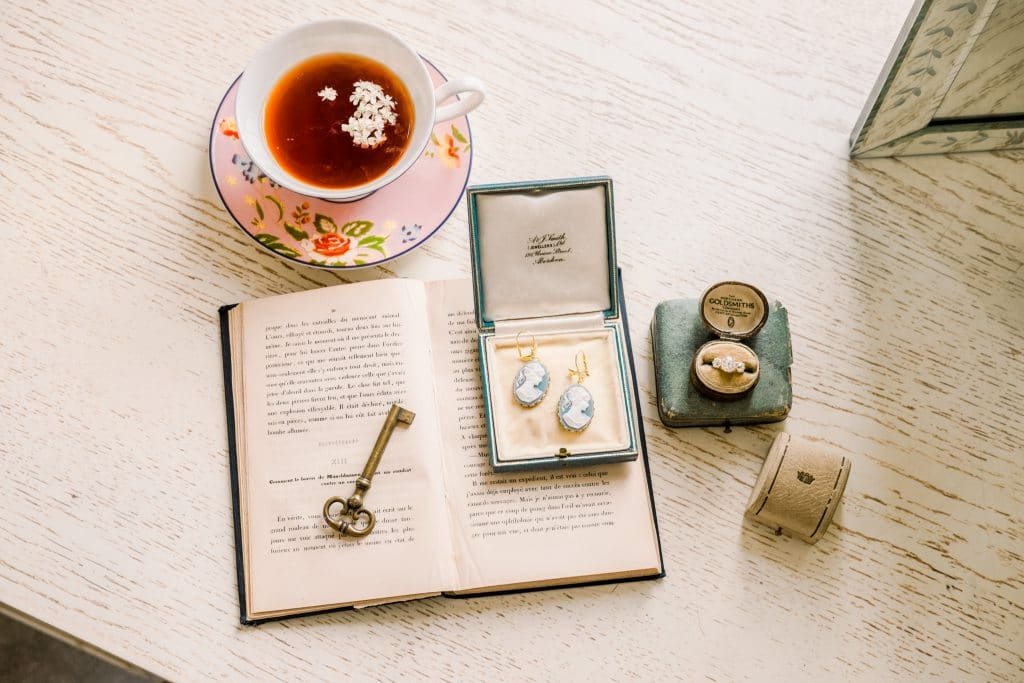 details of tea, antique key, book, and wedding bands