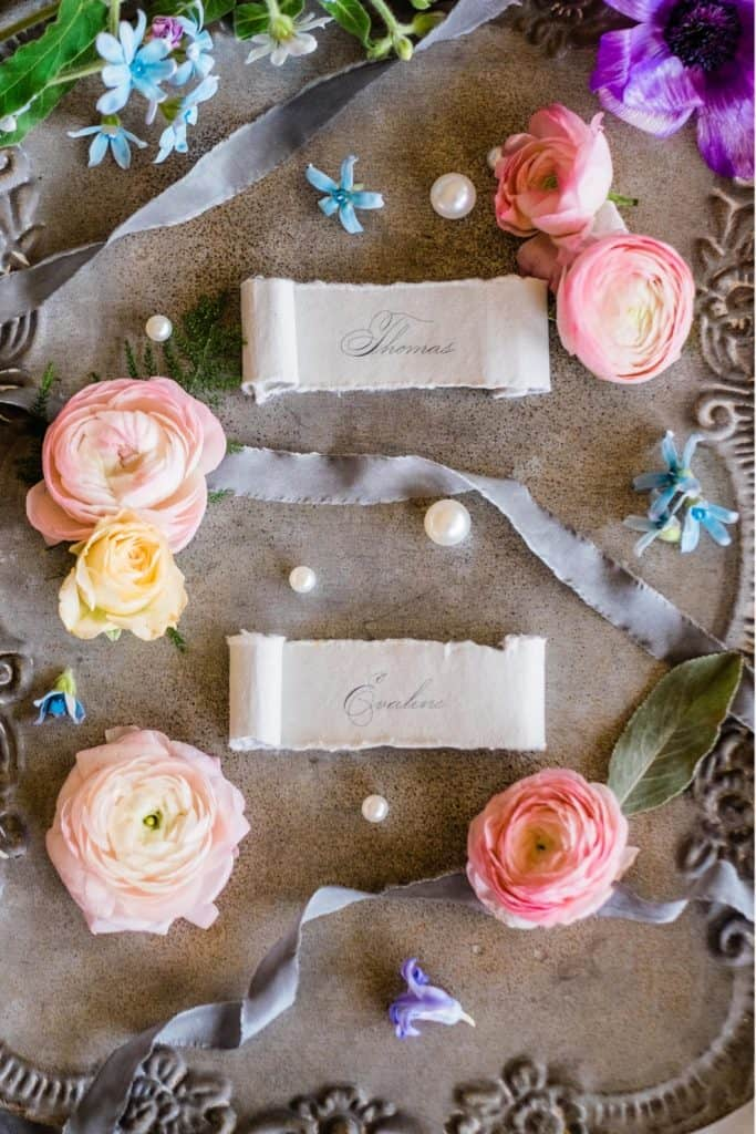 monogrammed ribbon laid on antique tray surrounded by colorful flowers