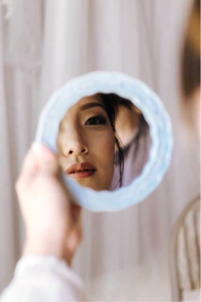 woman looking into mirror as she gets ready