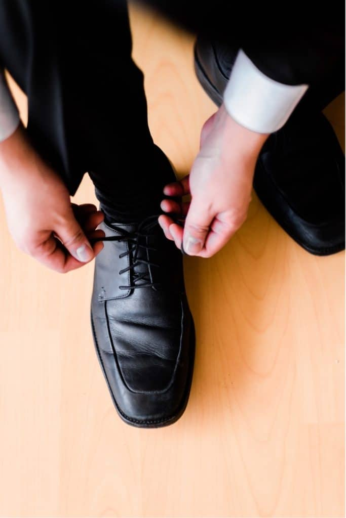 man in suit tying shoe laces