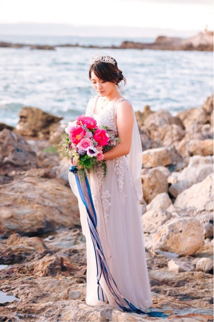 bride in purple gown and pearl crown holds colorful bouquet overlooking the ocean