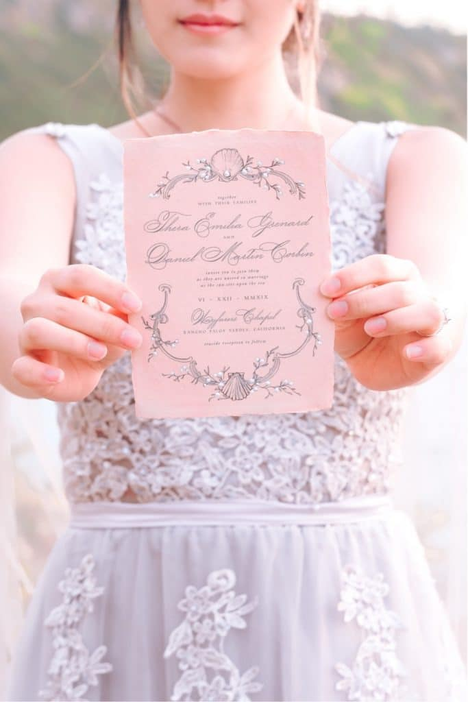 woman in purple wedding gown holds up elegant pink ocean-inspired wedding invitation