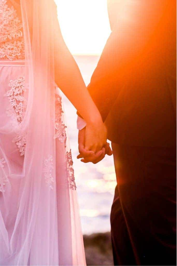 bride and groom hold hands on rocky outcropping overlooking ocean and colorful sunset