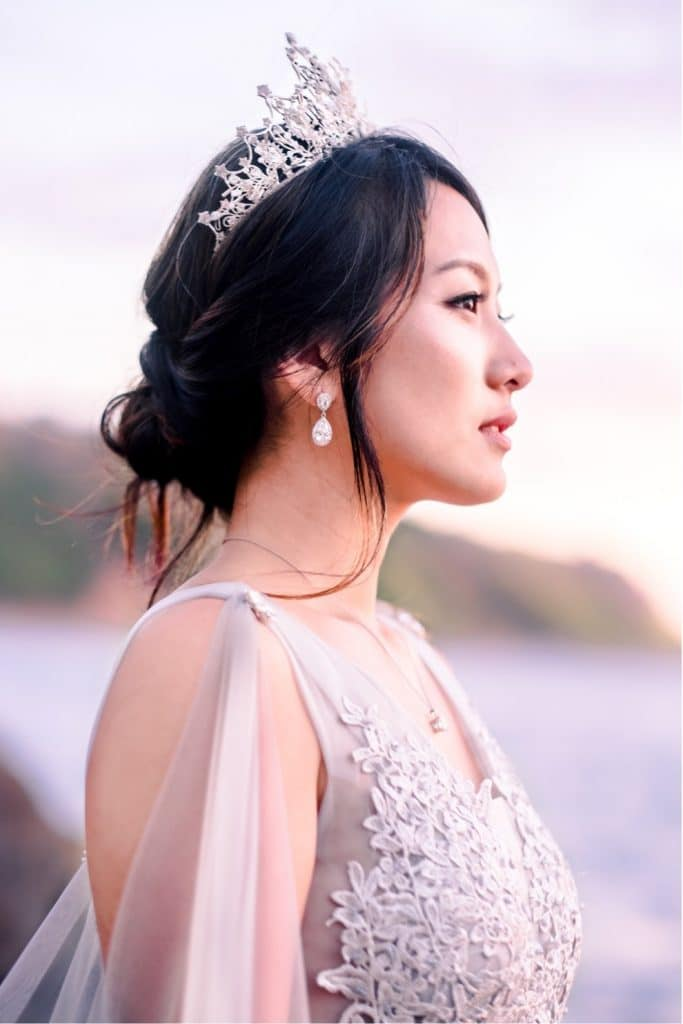 bride stands on rocky outcropping overlooking ocean and colorful sunset