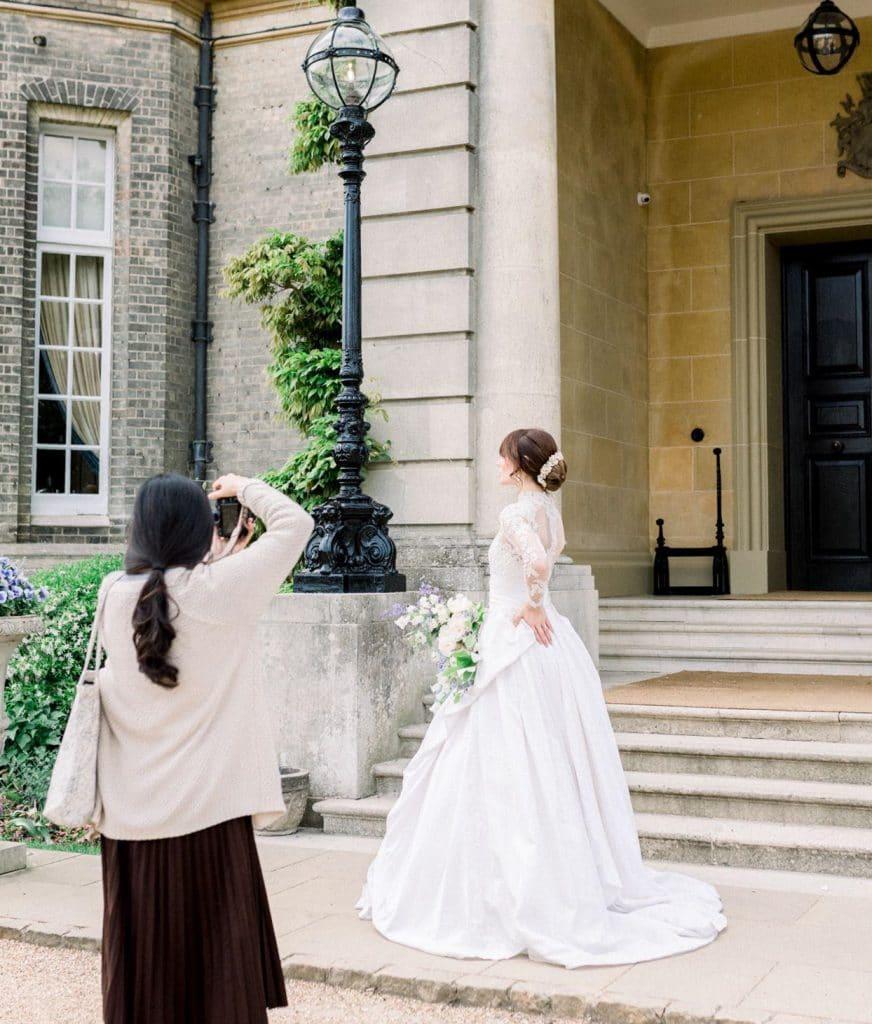 female photographer capturing portraits of bride on wedding day