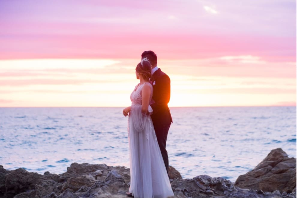 bride and groom embrace  on rocky outcropping overlooking ocean and colorful sunset