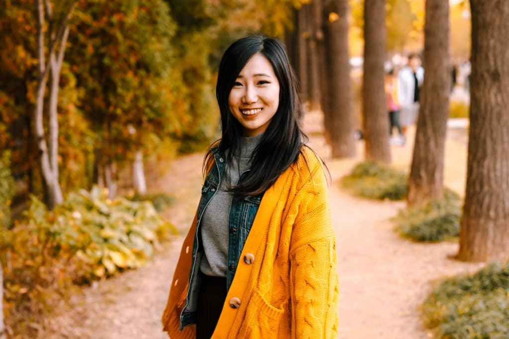 Cute girl in a yellow jacket smiling at camera