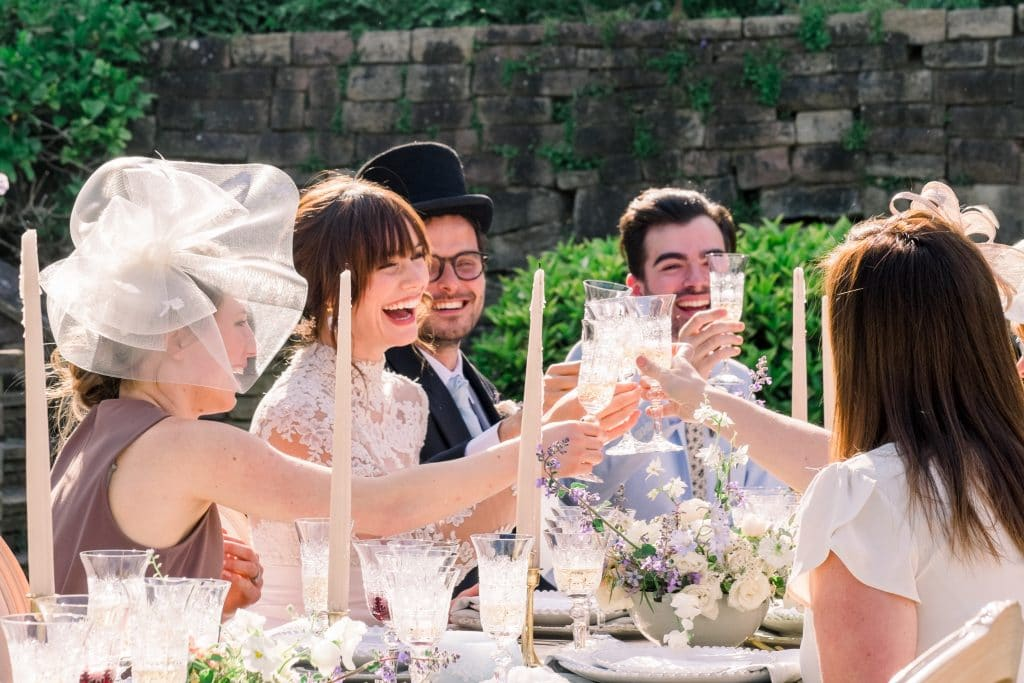 bride and groom dining with guests at outdoor garden wedding in UK