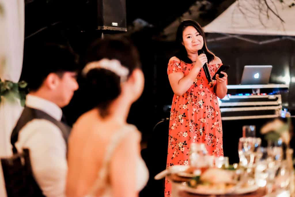 maid of honour giving speech at night time wedding reception