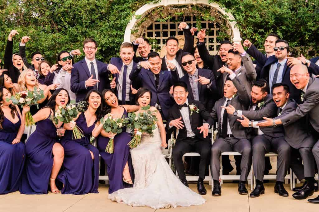 bridal party in gowns and suits doing fun, silly poses