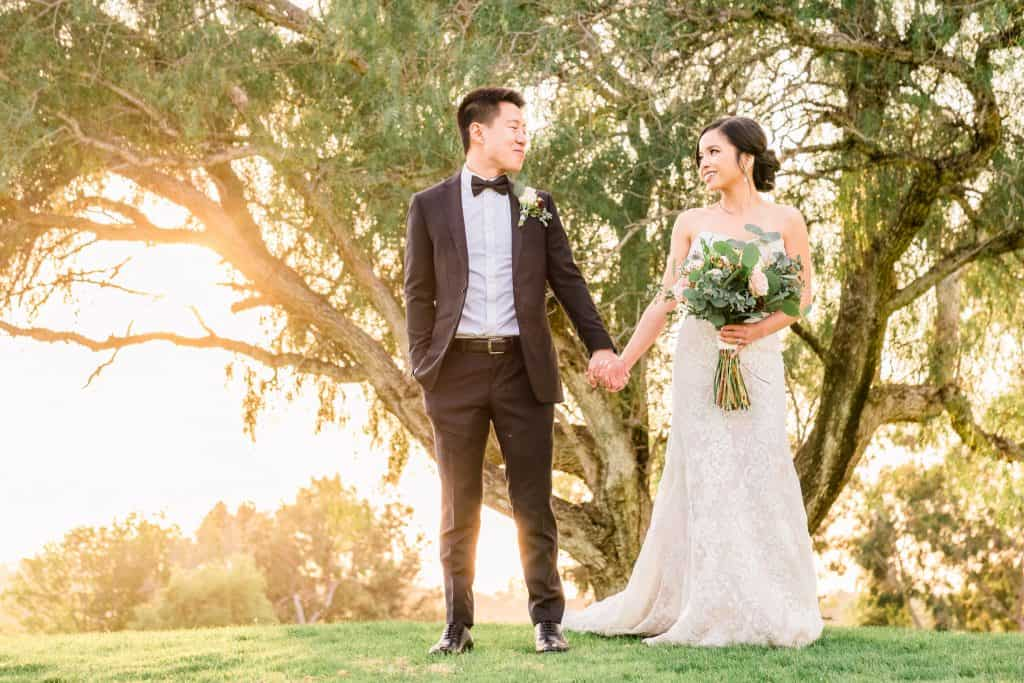 bride and groom hold hands while sun sets behind them