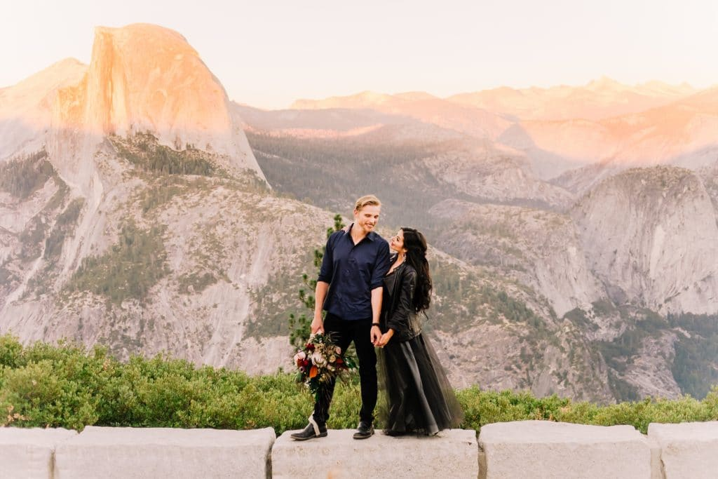 young couple dressed in black stand in front of sunlit mountain range