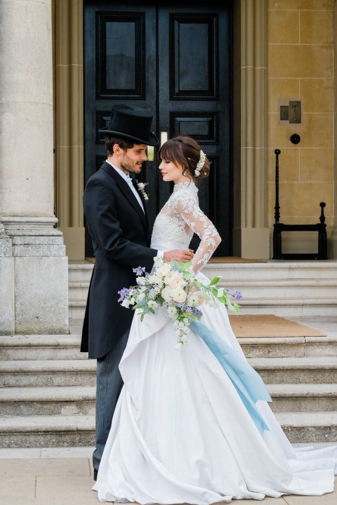 bride and groom stand in front of ornate doorway for UK destination wedding