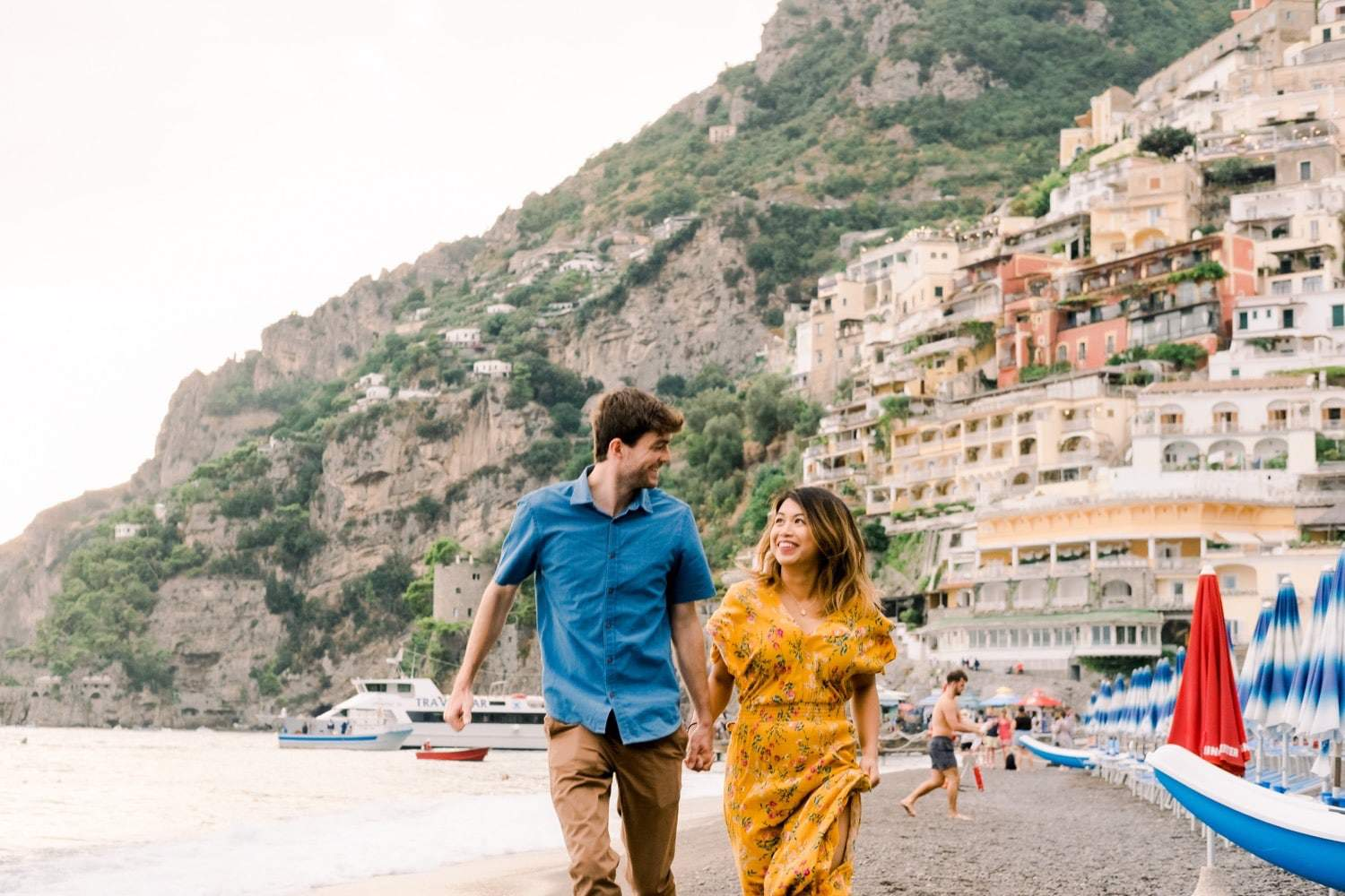young couple running along the beach in Italy's Amalfi Coast